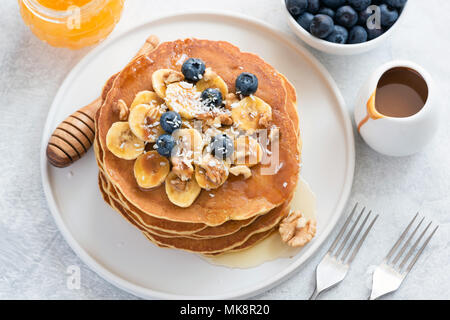 Pancakes with blueberries, banana, walnuts and honey on white plate. Stack of tasty pancakes with caramel syrup. Pancakes Breakfast with Honey - Stock Photo