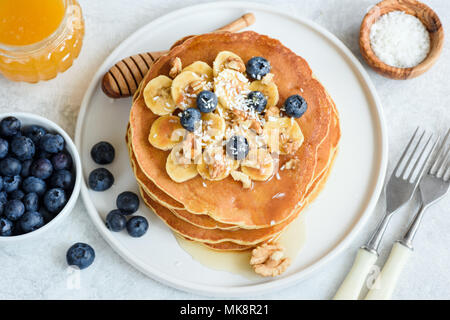Tasty Pancakes with Bananas, Blueberries, Walnuts and Honey on White Plate. Closeup view. Stack of Homemade Pancakes. Pancakes Breakfast Food - Stock Photo