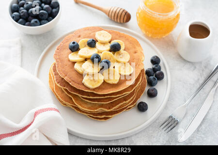 Pancakes stack with banana, blueberries and honey. Homemade american pancakes on white plate. Breakfast concept, horizontal composition - Stock Photo