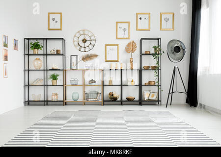 Spacious living room interior with lots of decorations on gold and black racks standing against a white wall with pictures gallery - Stock Photo
