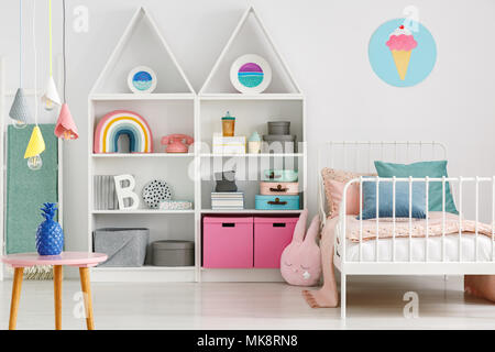 Colorful lamps above table in folk child's bedroom interior with ice cream poster above bed - Stock Photo