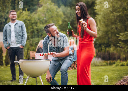 Smiling woman in a red dress drinking beer and her friend grilling a shashlik - Stock Photo
