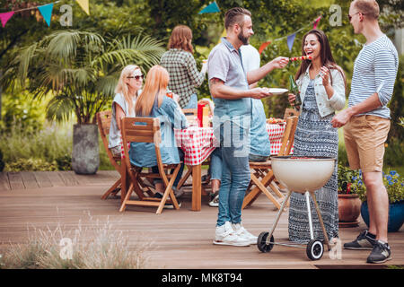 Man sharing a shashlik with his girlfriend drinking beer during friend's birthday party in the garden - Stock Photo