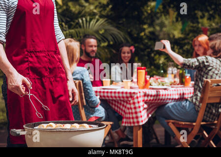 Close-up of man grilling food during outdoor birthday party in the summer - Stock Photo