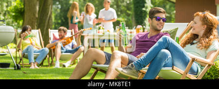Young couple talking during a grill party in the countryside - Stock Photo