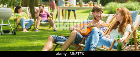 Young man playing guitar music for a girl during barbecue party