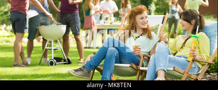 Girls having fun conversations during party in countryside - Stock Photo