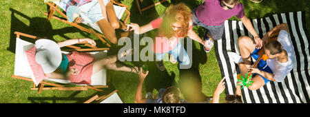 Young people having summer party in a garden - Stock Photo