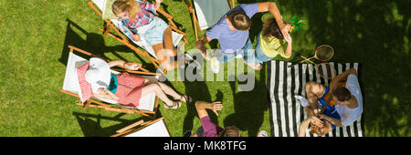 Friends spending time in a garden together dancing and resting - Stock Photo
