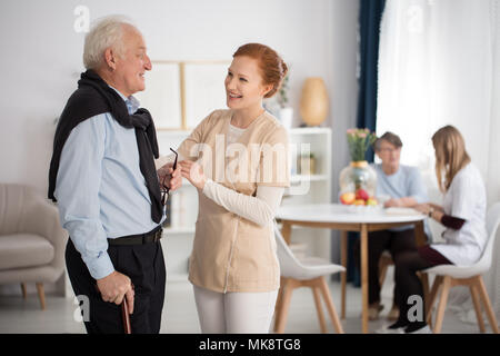 Tender attention of medical staff towards elderly man and woman, talking, explaining, comforting in luxury care facility common room