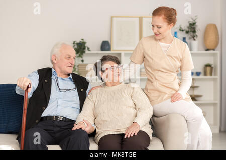 Professional assistant supporting and consoling a worried senior married couple in a living room of a day care center - Stock Photo
