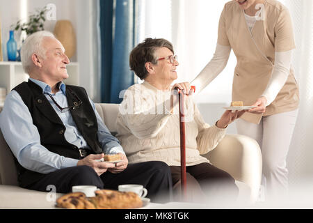 Geriatric couple with arthritis sitting on a couch and being served a piece of cake while waiting for a doctor's appointment at a luxury private clini - Stock Photo