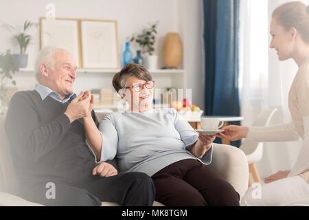 Young at heart emotional senior couple holding hands while sitting on settee and being served by a caregiver a cup of tea in a sunny living room at ho - Stock Photo