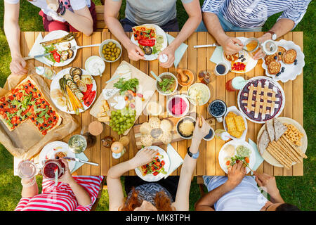 Friends eating healthy food like vegan pizza and fruit outdoors in the park on a rustic table - Stock Photo