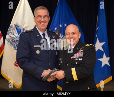U.S. Air Force Gen. John Hyten, commander of U.S. Strategic Command, presents an Army general officer's pistol to U.S. Army Brig. Gen. Thomas James at Peterson Air Force Base, Colorado, Nov. 14, 2017.  Hyten presided over James' promotion to brigadier general.  James serves as deputy commander of Joint Functional Component Command for Space, which is a component of USSTRATCOM responsible for executing continuous, integrated space operations.  (U.S. Air Force photo by Dave Grim) - Stock Photo