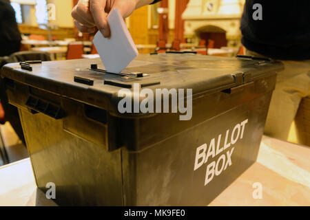 Person posting a vote into a ballot box during an election - Stock Photo
