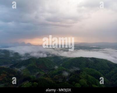 Morning fog drifts through low hills, seen from Takataniyama Camp Ground near Miyoshi, Japan - Stock Photo
