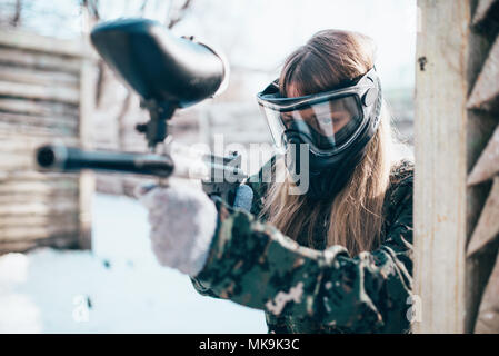 Female paintball player with marker gun in hands, winter forest battle. Extreme sport game, woman fights in protection mask and uniform - Stock Photo