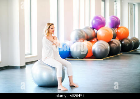 Young woman doing exercise with a fitball in a gym. Stock Photo