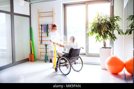 Young woman physiotherapist working with a senior man in wheelchair. - Stock Photo
