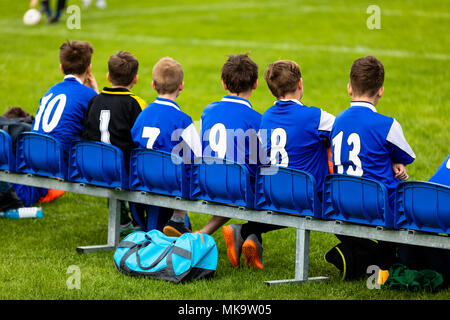 Kids Soccer Team on a Bench. Children Football Team Players. Young Boys in Blue Jerseys as a Substitute Soccer Players. Youth Footballers of Football  - Stock Photo