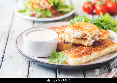 Crumbed golden fried fish fingers served with tartar sauce and salad on a white rustic wooden background - Stock Photo