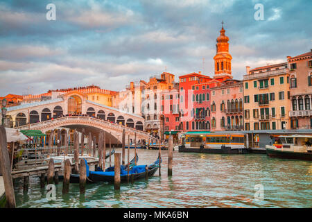 Classic panoramic view with traditional Gondolas on famous Canal Grande with famous Rialto Bridge in the background in beautiful golden evening light  - Stock Photo