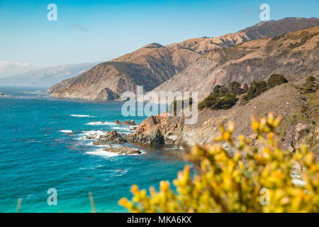 Scenic view of the rugged coastline of Big Sur with Santa Lucia Mountains and Big Creek Bridge along famous Highway 1 at sunset, California, USA - Stock Photo