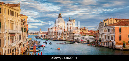 Classic view of famous Canal Grande with scenic Basilica di Santa Maria della Salute in beautiful golden evening light at sunset, Venice, Italy - Stock Photo