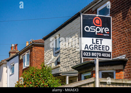 Let agreed sign outside a row of houses in a residential street, rental market concept, England, UK - Stock Photo