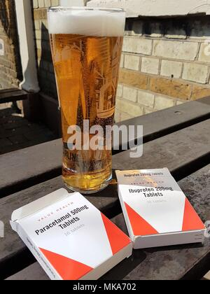 A pint of Carling lager and empty packets of Paracetamol and Ibuprofen on a wooden bench in a pub garden, hangover cure?. - Stock Photo