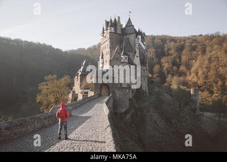 Classic view of young person in red jacket standing in front of famous Eltz Castle at sunrise in fall, Rheinland-Pfalz, Germany - Stock Photo