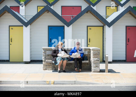 Colourful beach huts stand near the shore on a warm sunny afternoon in the coastal town of Swanage, Dorset, UK. - Stock Photo