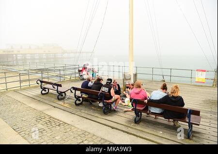 Aberystwyth  Wales UK, Monday 07 May 2018  UK Weather: People at the seaside in Aberystwyth enjoying the misty sunshine , on what is expected to be the hottest early May Bank Holiday Monday on record, with temperatures reaching 28ºc in parts of the south east of England   photo © Keith Morris / Alamy Live Newps - Stock Photo