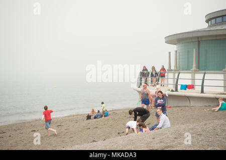 Aberystwyth  Wales UK, Monday 07 May 2018  UK Weather: People at the seaside in Aberystwyth in the chilly  and grey sea mist, on what is expected to be the hottest early May Bank Holiday Monday on record, with temperatures reaching 28ºc in parts of the south east of England   photo © Keith Morris / Alamy Live News - Stock Photo