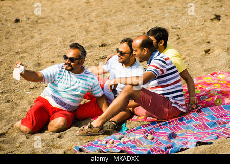 Aberystwyth  Wales UK, Monday 07 May 2018  UK Weather: After hours of chilly grey sea mists, the sun finally shone through on this group of men taking a selfie picture at the beach in Aberystwyth, , on what is expected to be the hottest early May Bank Holiday Monday on record, with temperatures reaching 28ºc in parts of the south east of England   photo © Keith Morris / Alamy Live News - Stock Photo