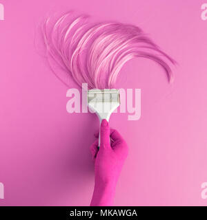 Hand holding paintbrush with long hair minimal abstract pink creative concept. - Stock Photo
