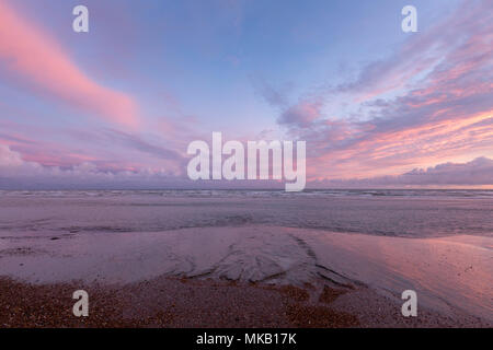 A pink cloudburst at sunset with the tide out on the beach at Brighton., East Sussex, UK. - Stock Photo