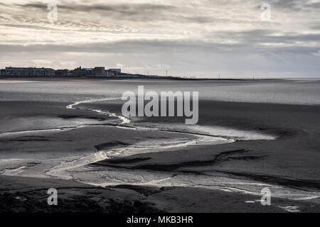 A stream meanders through mudflats at low tide in Morecambe Bay, with the seafront of Sandylands and Heysham Power Station in the background. - Stock Photo