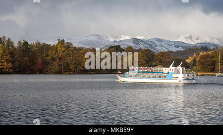 A passenger fery crosses Windermere lake from Ableside pier, past autumn woodland the snow-capped mountains of Langdale, in England's Lake District Na - Stock Photo