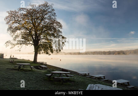 Mist rises from Windermere lake on a frosty autumn morning at Ambleside in England's Lake District National Park. - Stock Photo