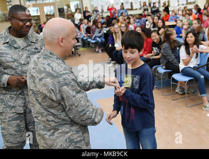 Col. Roman Hund, installation commander, presents a pin to Asher Schultz, a fifth grader at Hanscom Middle School, during an assembly at the school Nov. 17, as Chief Master Sgt. Henry Hayes, Hanscom's command chief, looks on. Hund and Hayes were on hand to present awards to approximately 50 students at the school. (U.S. Air Force photo by Linda LaBonte Britt) - Stock Photo