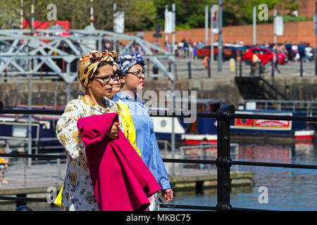 Three women wearing colourful headscarves enjoy a sunny afternoon in Liverpool. - Stock Photo