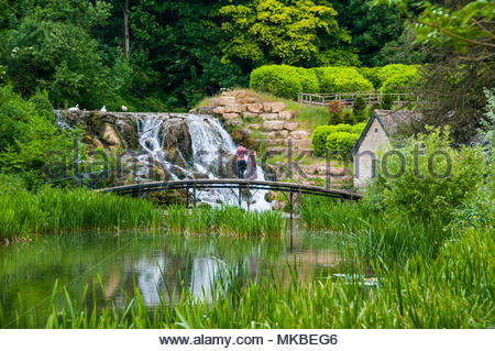 A couple on a bridge in front of the Grand Cascades in the landscaped gardens of Blenheim Palace, Oxfordshire, England. - Stock Photo