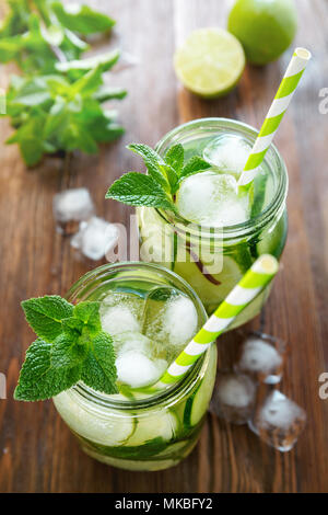 Two jars of fruit and herb infused water with cucumber, lime, mint and ice pieces on a wooden table. The concept of detox and weight loss. - Stock Photo