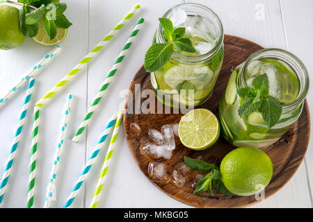 Two jars of fruit and herb infused water with cucumber, lime, mint and ice pieces on a wooden board. Cocktail paper rolls are scattered on a table. Th - Stock Photo
