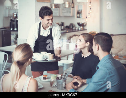 Polite smiling waiter bringing ordered dishes to friends in tearoom of a cozy confectioner's shop - Stock Photo