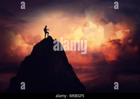 Self overcome concept as a businessman climbing a tall mountain over the clouds. Road to win and succes over sunset background. Achieving goals symbol - Stock Photo