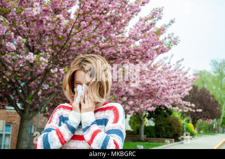 Young woman blowing nose near blooming tree. Spring allergy concept - Stock Photo