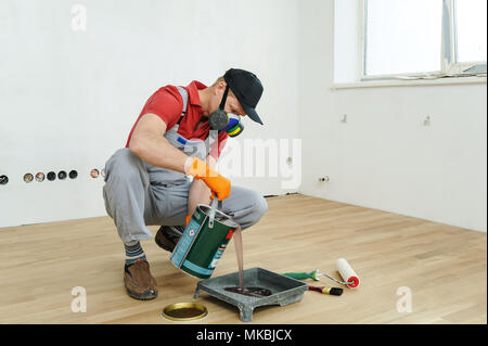 Lacquering wood floors. Worker pours floor lacquer in the tray. - Stock Photo